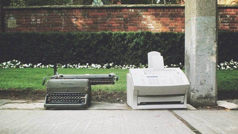 maquina de escribir y telefax en el suelo de la calle